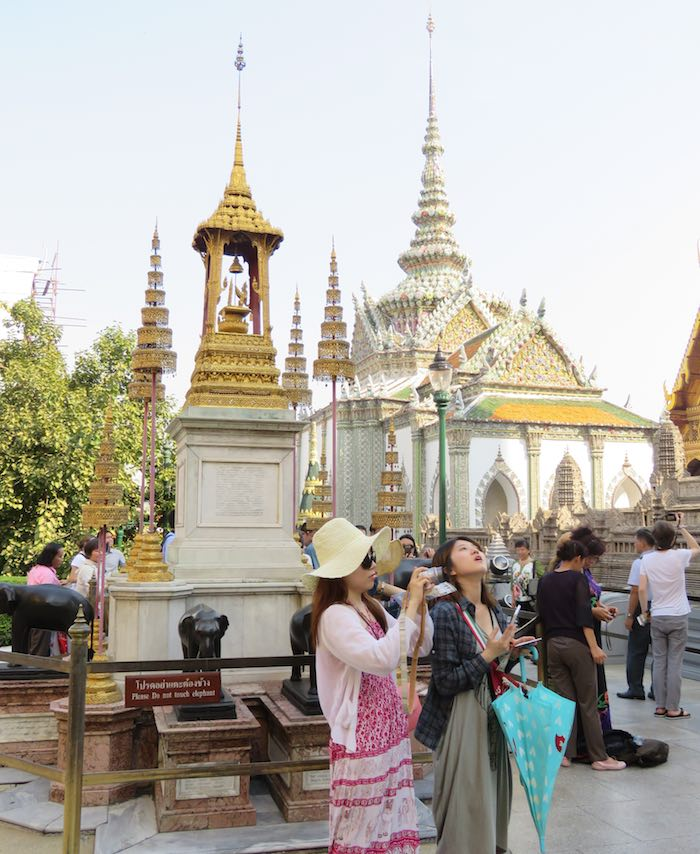 Tourists looking up at the Grand Palace