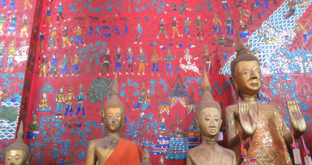 buddha statues in front of a mosaic wall inside Wat Xieng Thong temple building