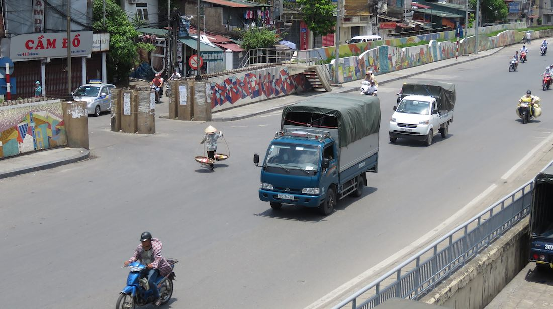 Roadway with person crossing and view of the Hanoi Mosaic Mural
