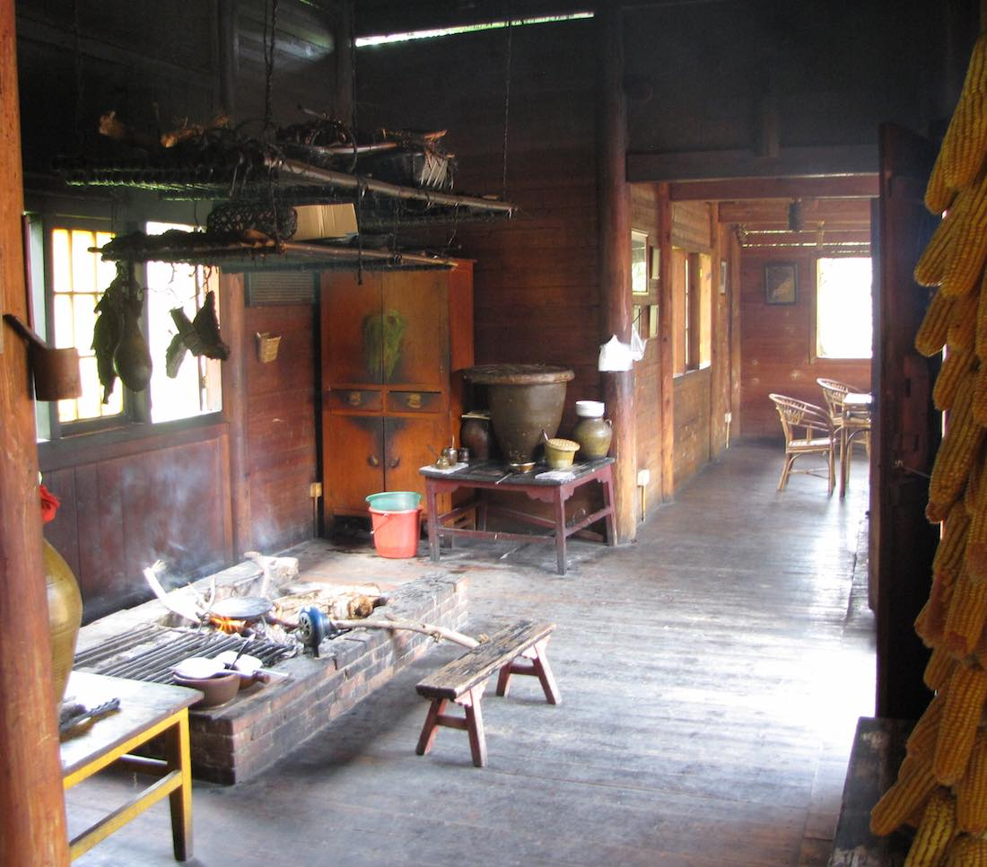 Inside traditional Yunan wooden house with open brick fireplace