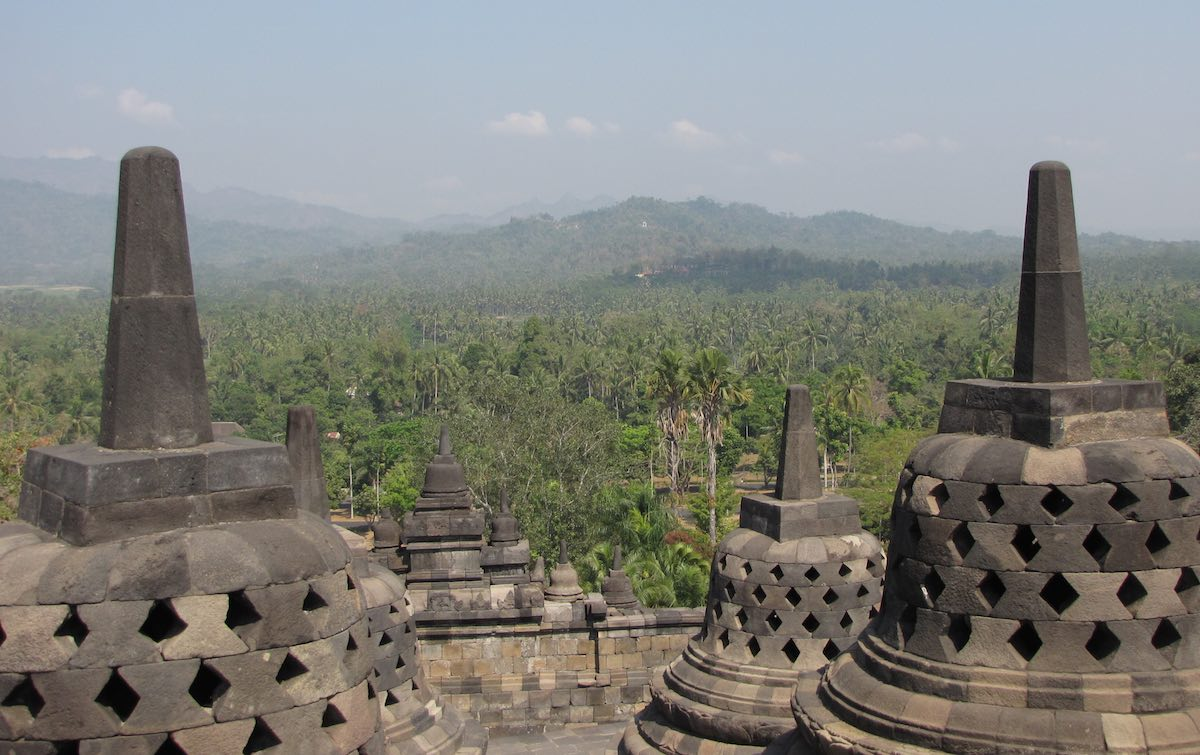 Lush green forests surrounding Borobudur with stupas in the foreground