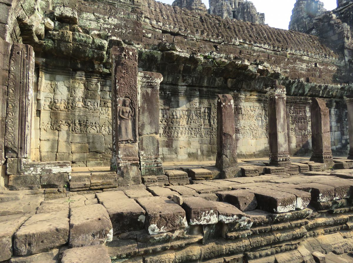 Covered stone walkway with art relief on the walls at Bayon