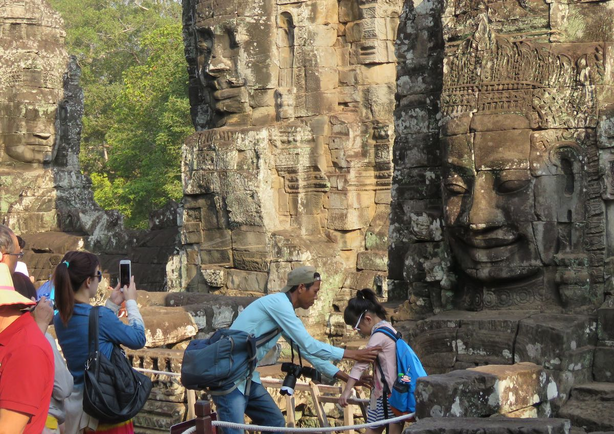 Tourists taking photos in front of many carvings of faces