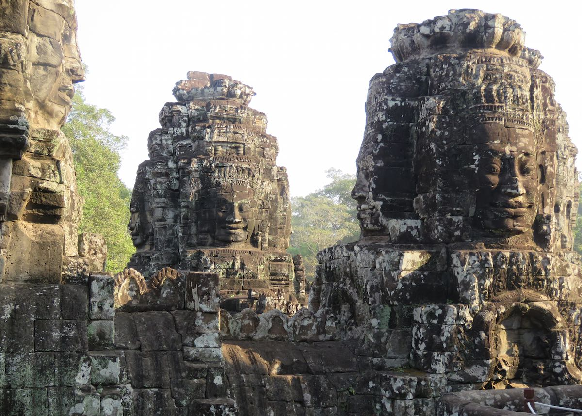 many carved faces with trees in the background