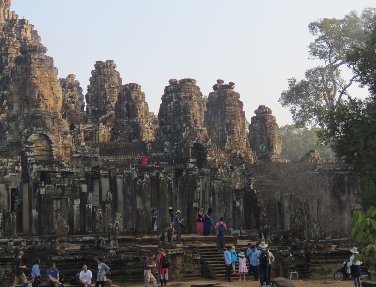 wide shot of Bayon Temple with tourists dwarfed by the size of the temple