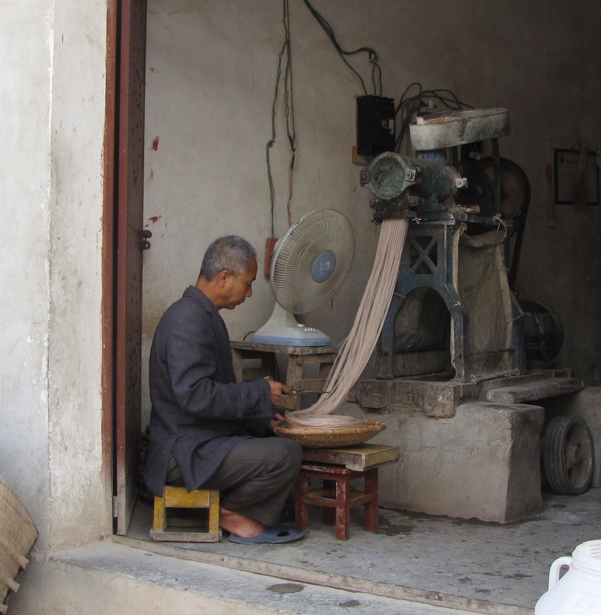 Seated Man using a machine to make noodles
