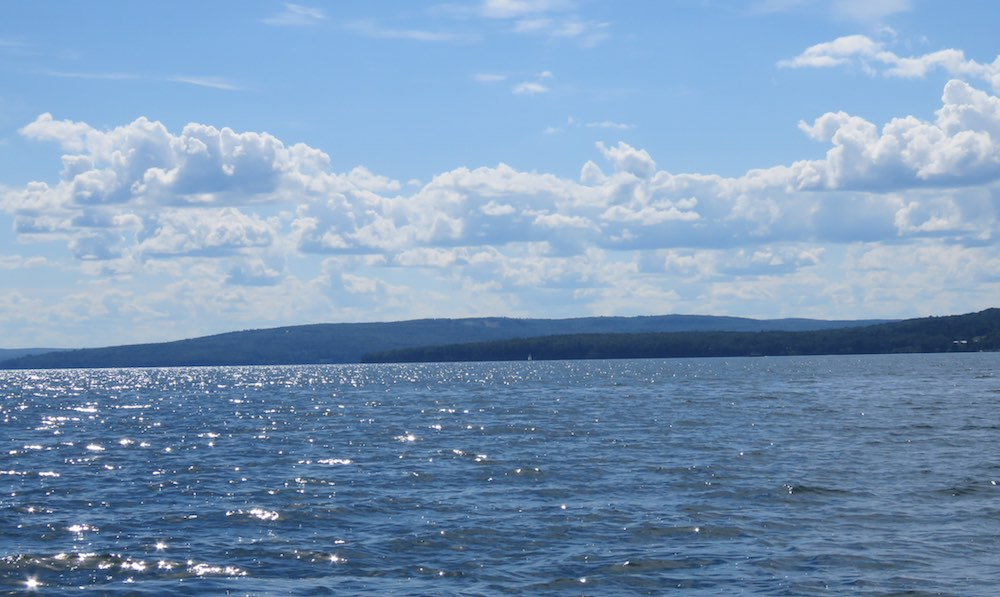 photo of Lake Superior with shimmering blue water, clouded blue sky and islands on the horizon