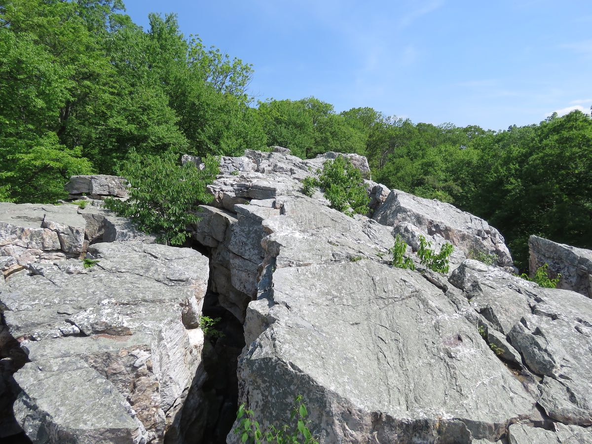 Fractured rock overview with trees and sky in the background