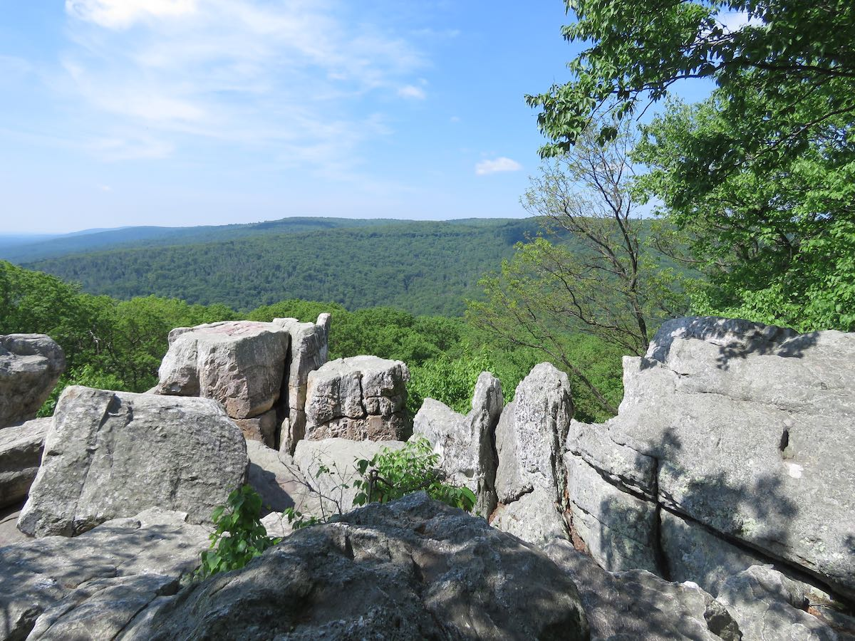 Rock overlook with vista of forest and blue sky